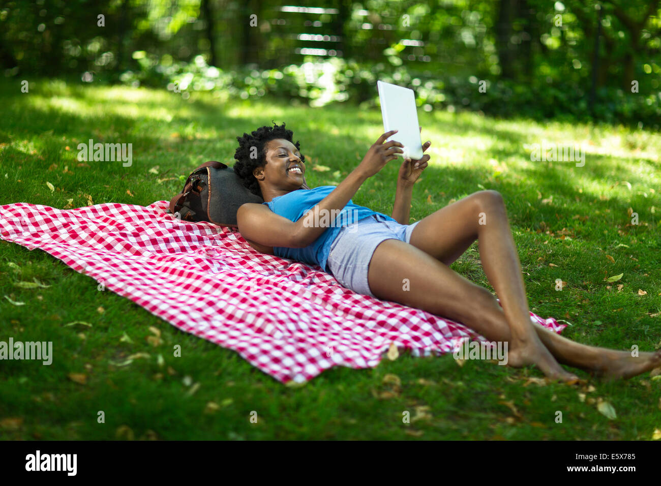Young woman lying in park looking up at digital tablet - Stock Image
