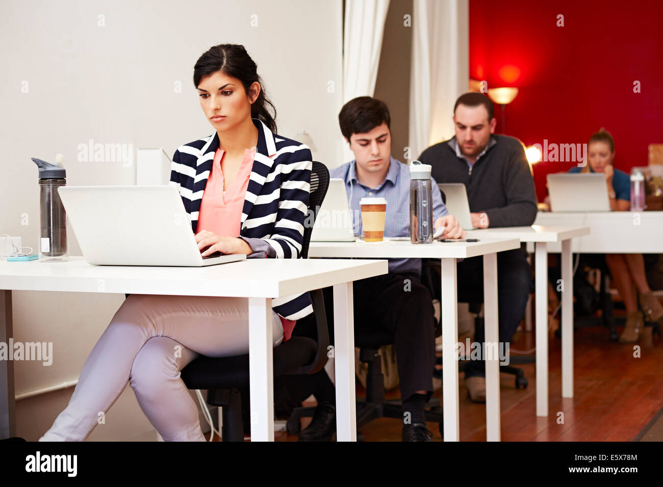 Row of people working on laptops in office - Stock Image