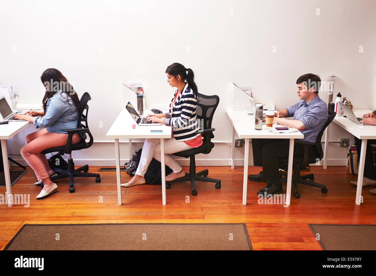 Row of people working at desks in office - Stock Image
