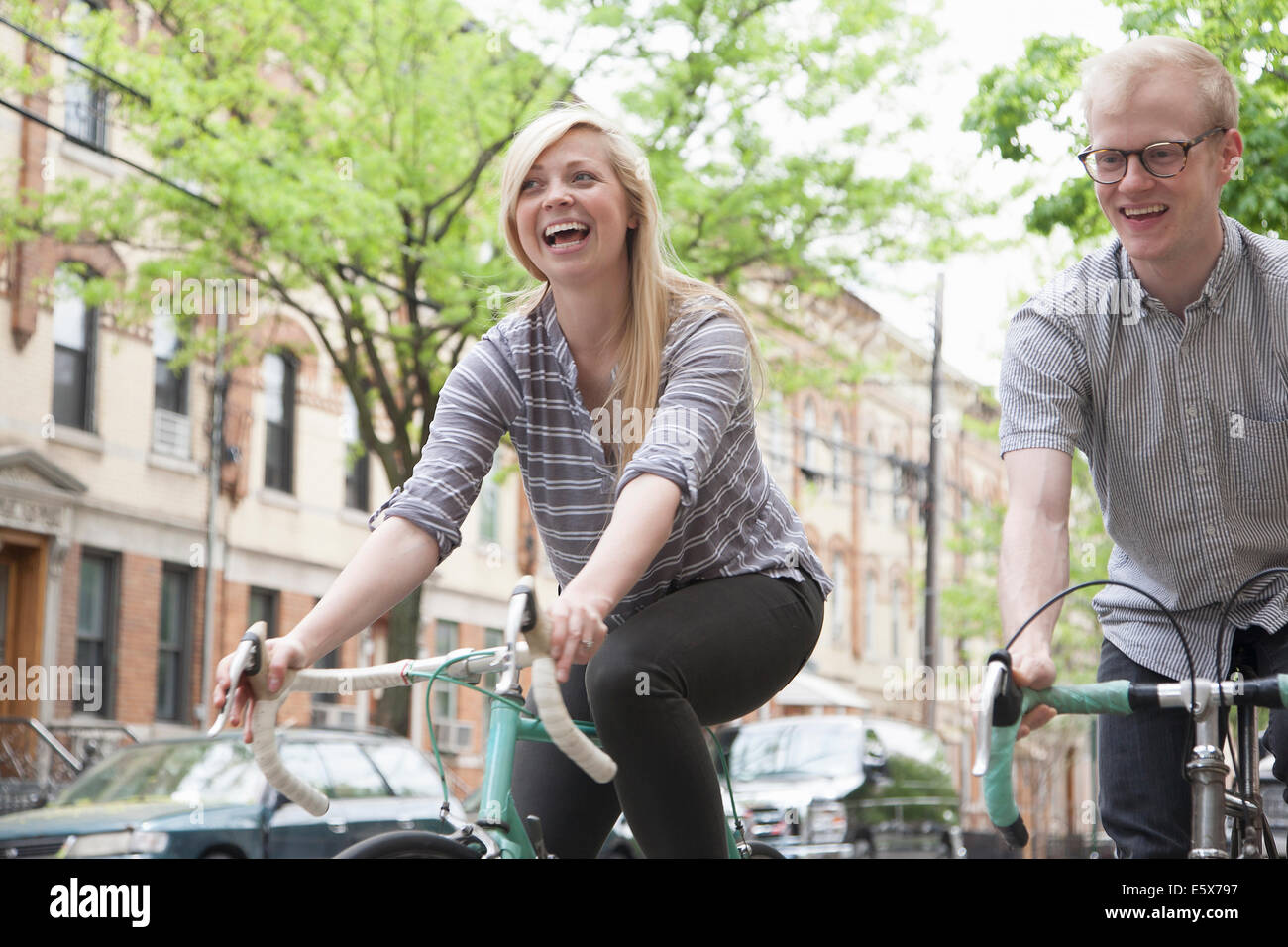 Young couple laughing whilst cycling along street - Stock Image