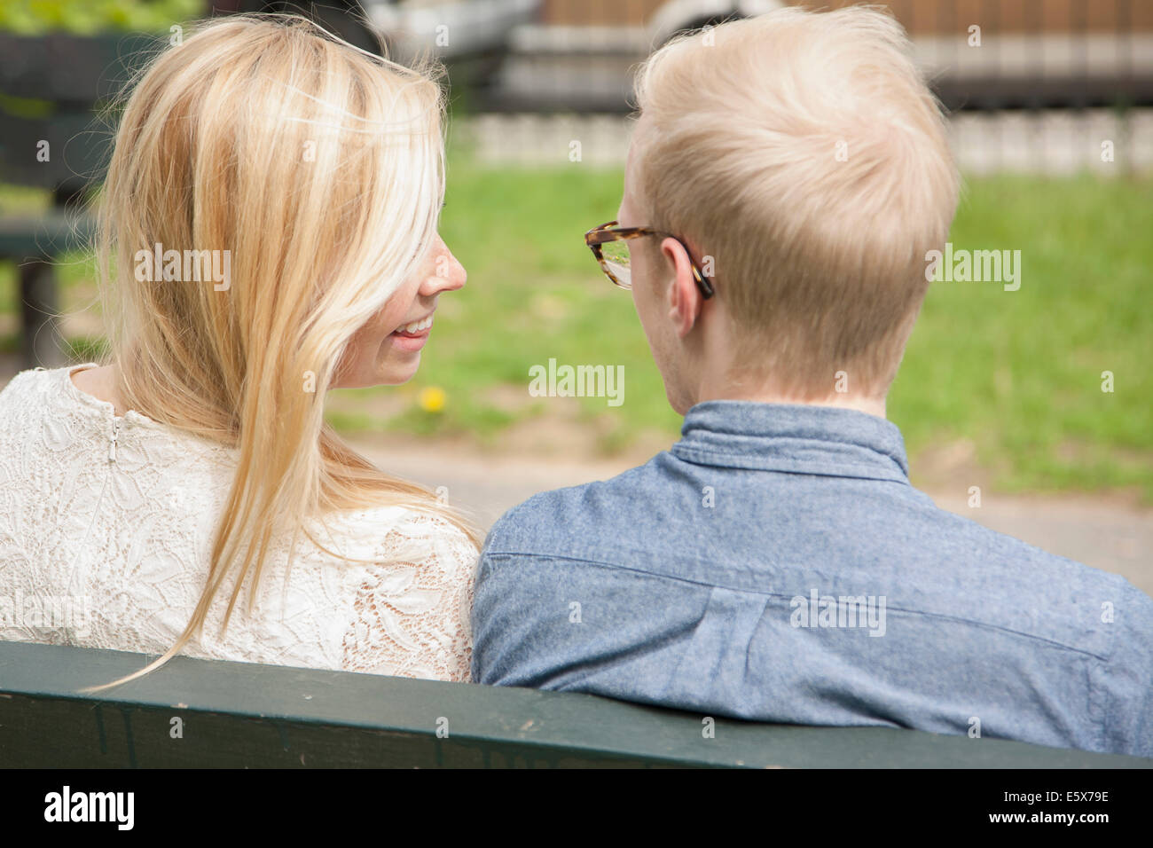 Over the shoulder view of young couple on park bench - Stock Image