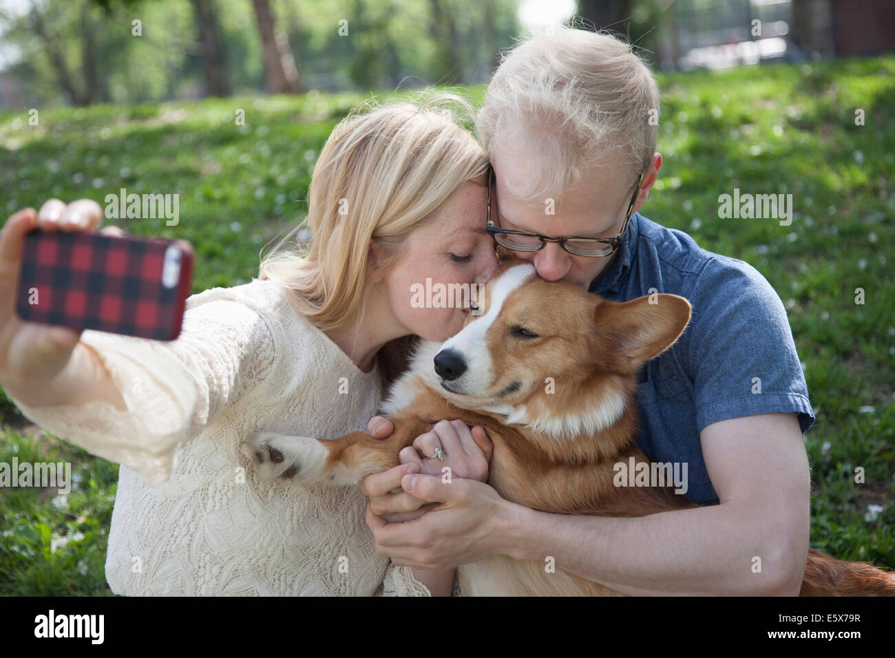 Young couple in park taking selfie whilst kissing corgi dog - Stock Image