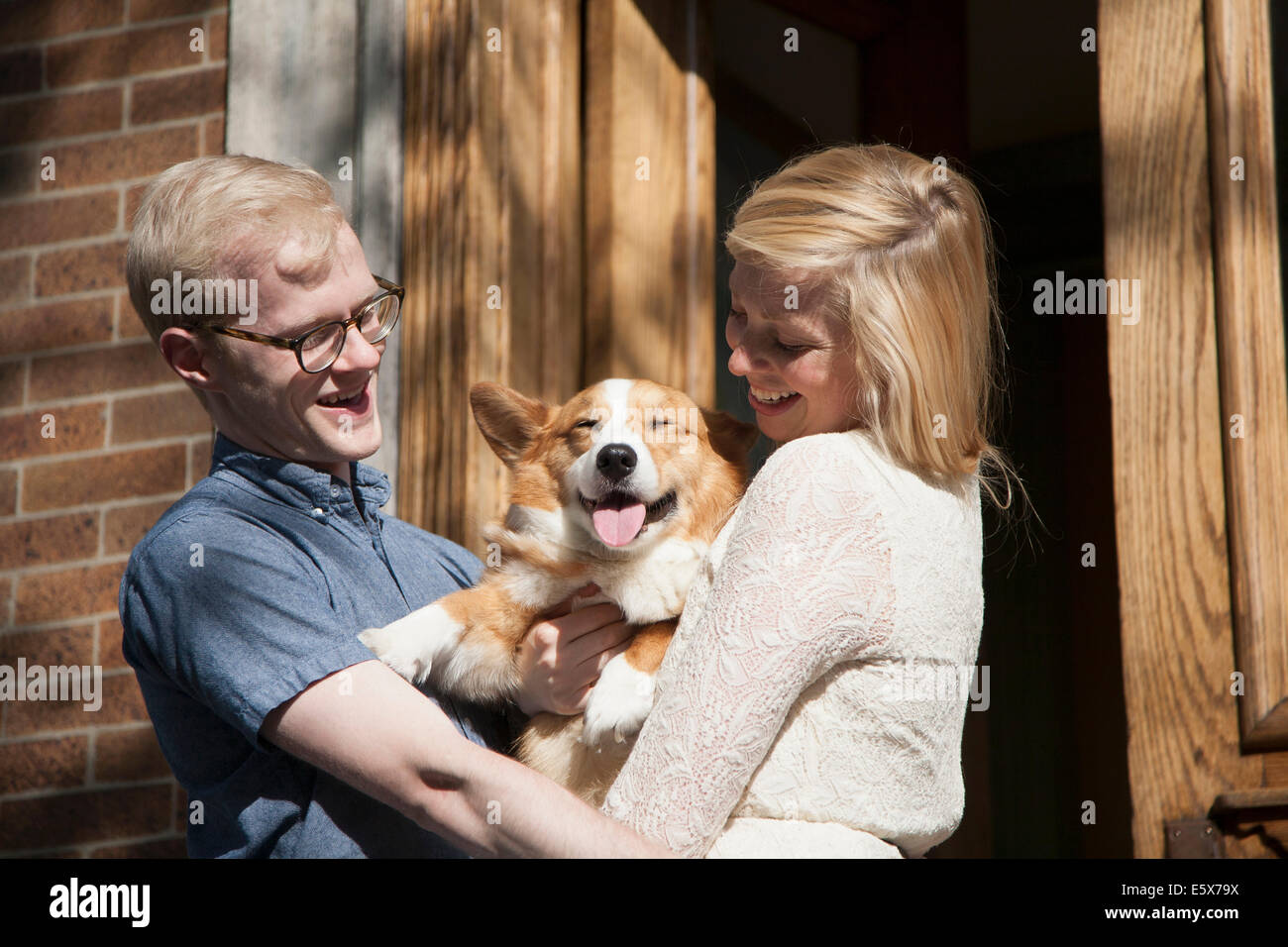 Happy young couple with corgi dog in arms outside front door - Stock Image