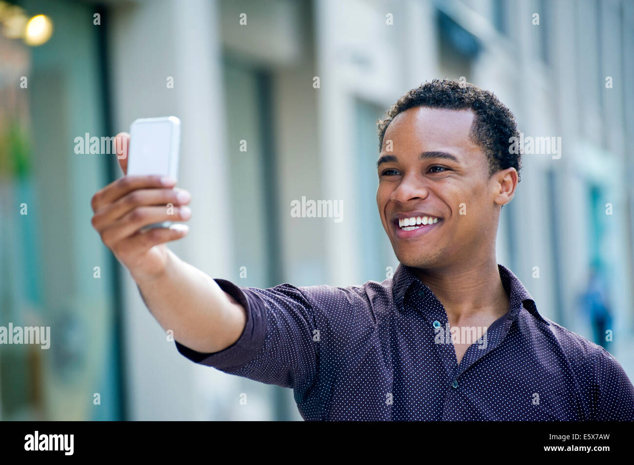 Young man taking smartphone selfie on city street - Stock Image