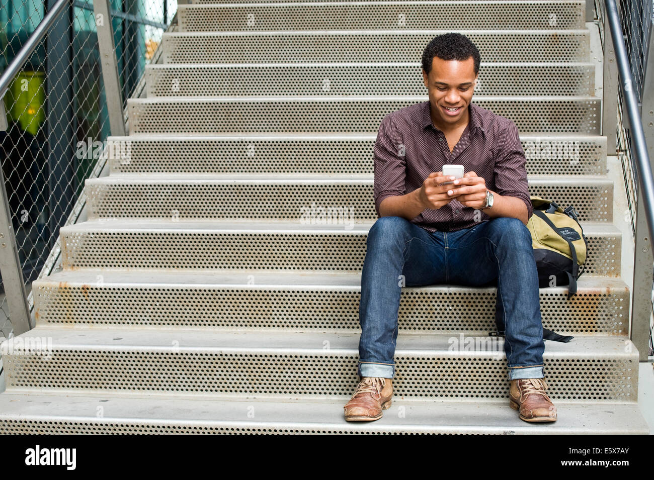 Young man texting on smartphone on city stairway - Stock Image
