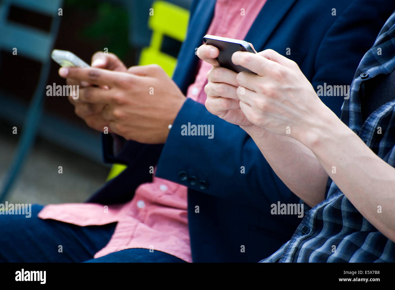 Cropped torso shot of young businessmen in city park texting on smartphones - Stock Image