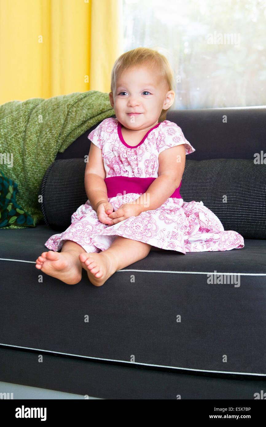 Portrait of shy baby girl sitting on sofa - Stock Image