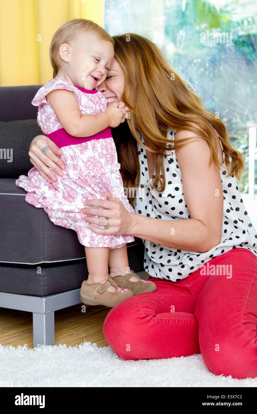 Mid adult mother and baby daughter sharing a tender cuddle - Stock Image