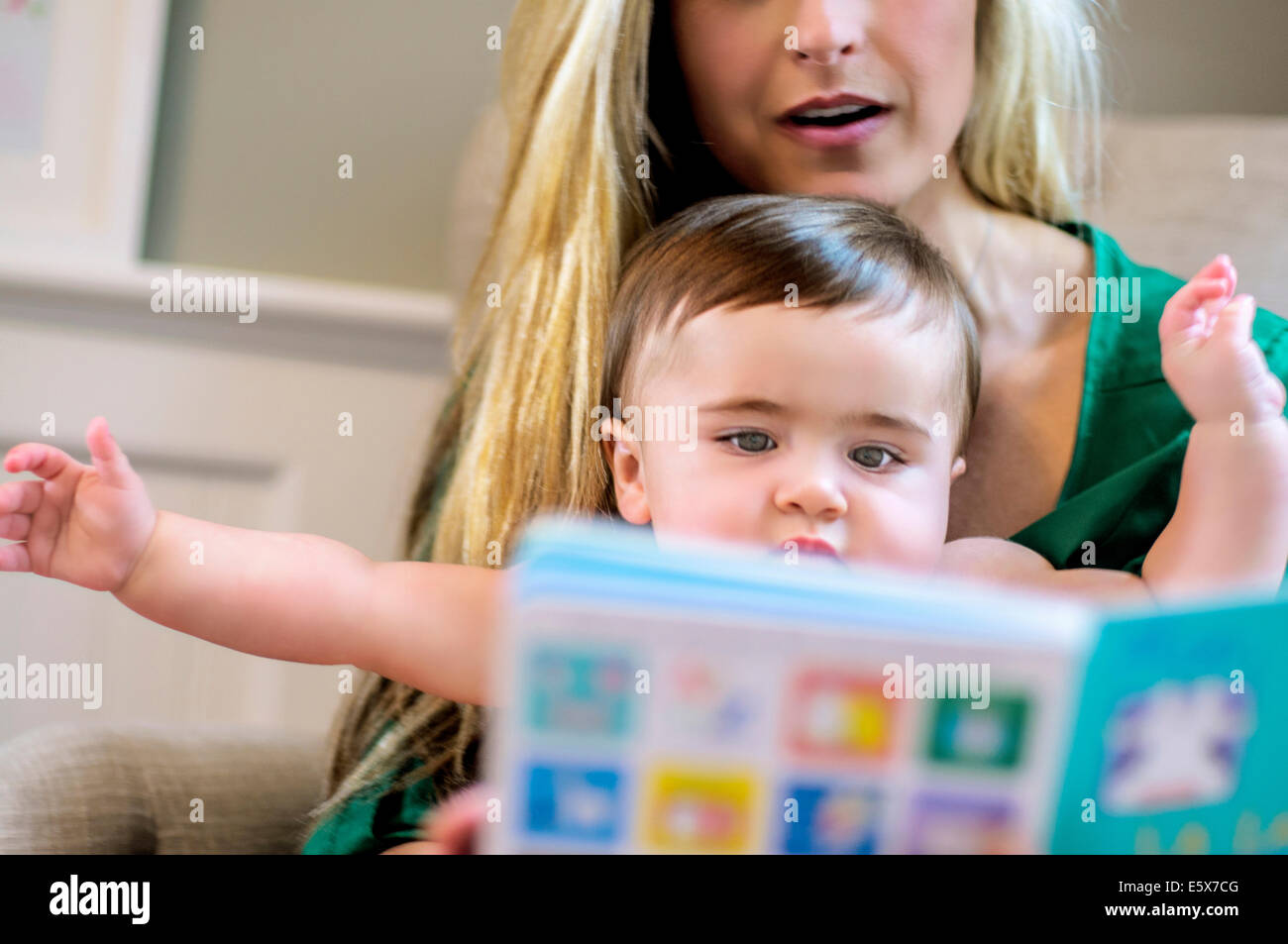 Mid adult mother reading picture book to baby daughter - Stock Image