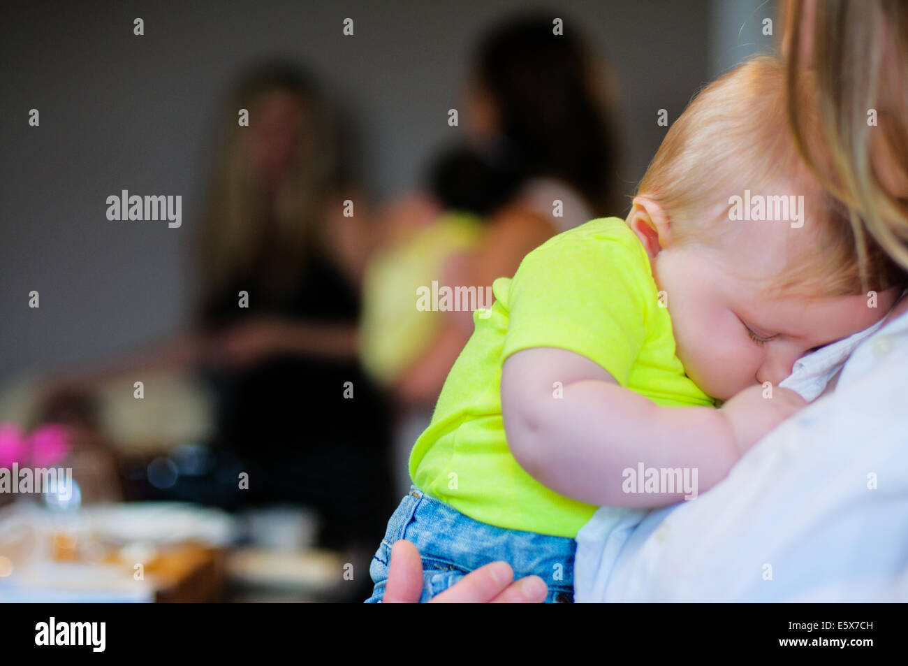 Close up of baby boy asleep on mother's shoulder - Stock Image