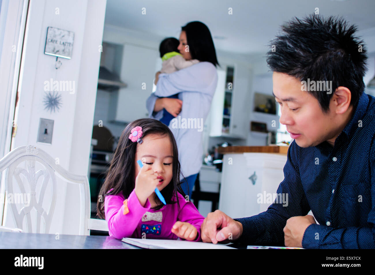 Mid adult father teaching toddler daughter in kitchen Stock Photo