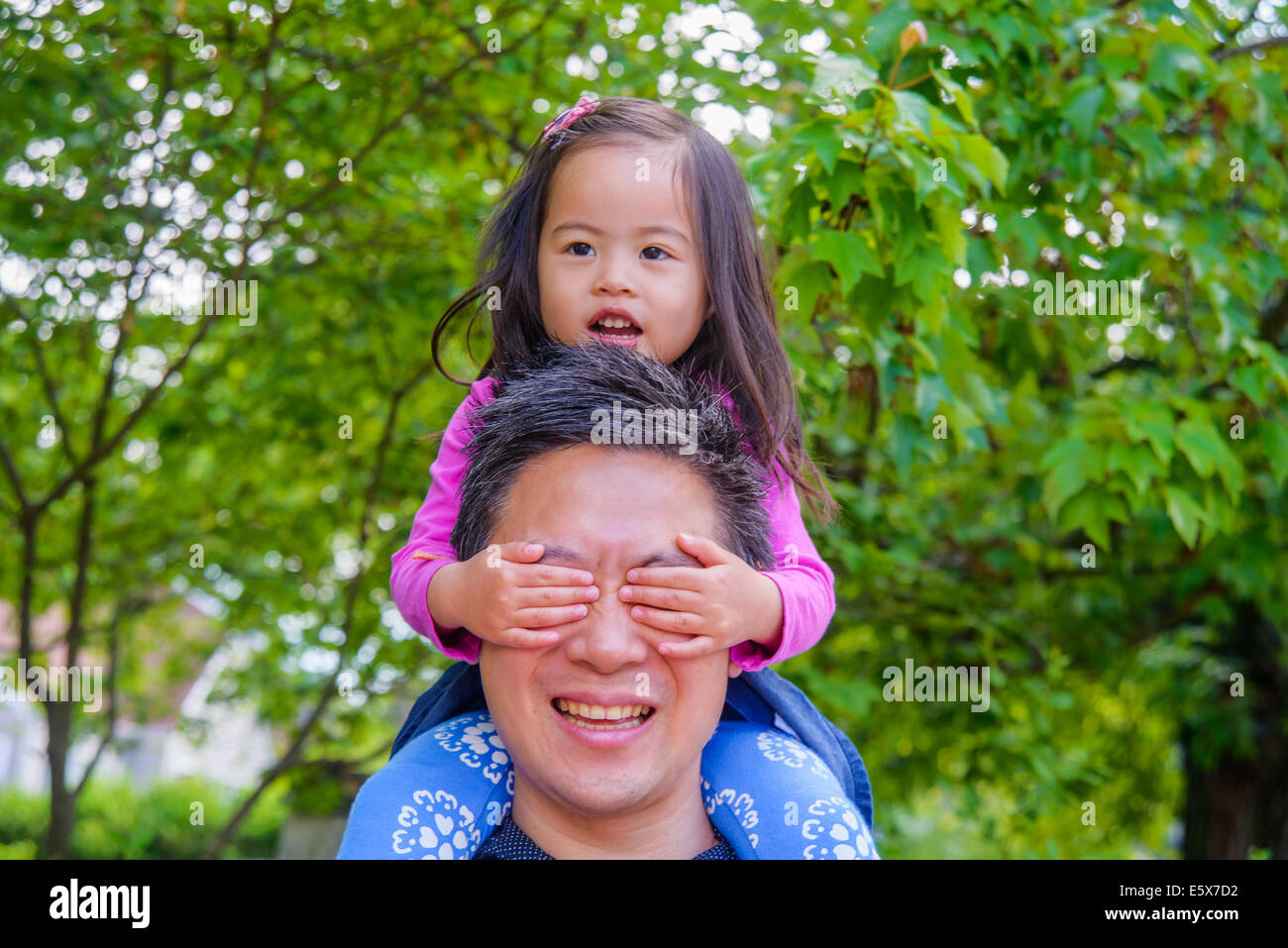 Mid adult father shoulder carrying toddler daughter in garden Stock Photo