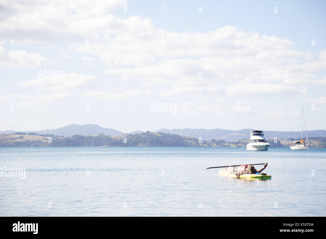 Mid adult woman lying on her back paddleboarding at sea - Stock Image