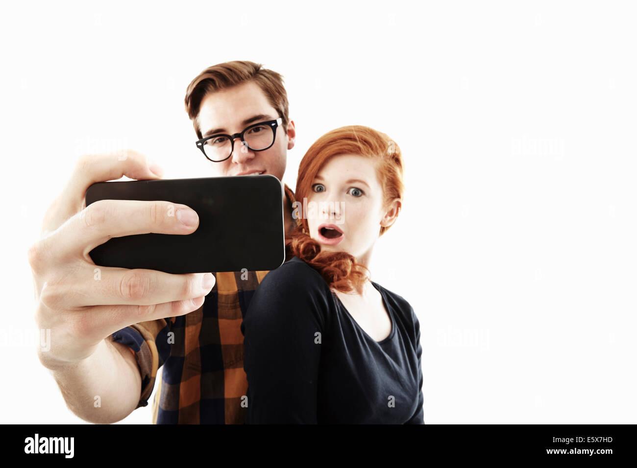 Studio shot of young couple posing for selfie on smartphone - Stock Image
