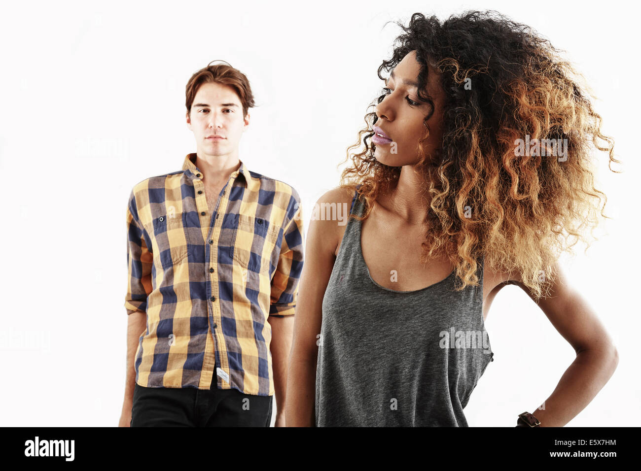 Studio portrait of confident young woman in front of young man - Stock Image
