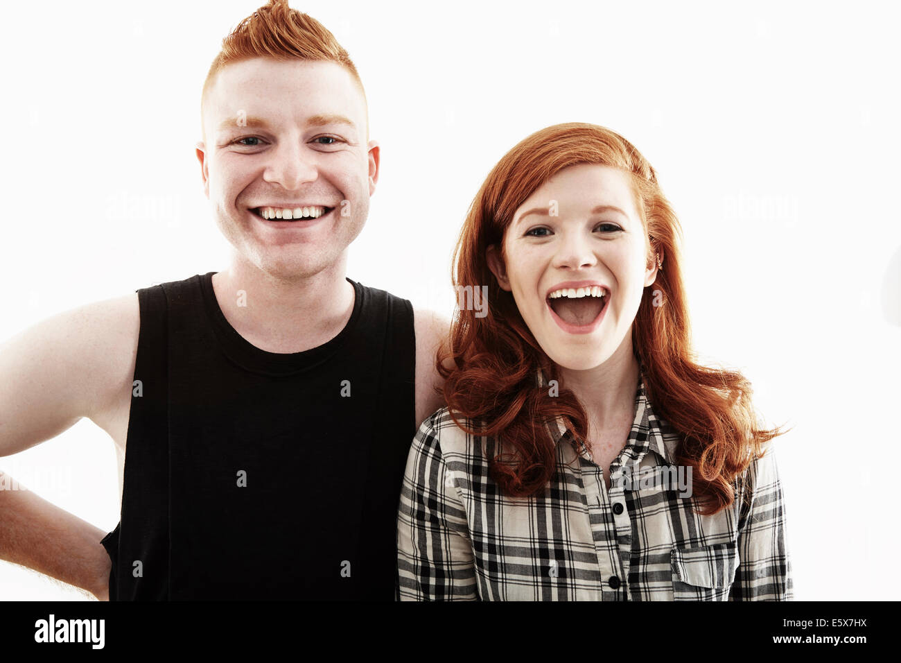 Studio portrait of red haired young couple laughing - Stock Image