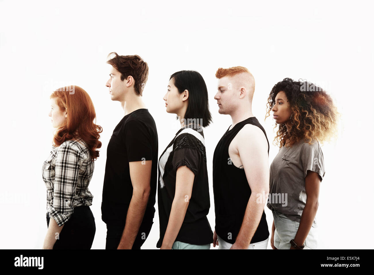 Side view studio portrait of five young adults in a row - Stock Image