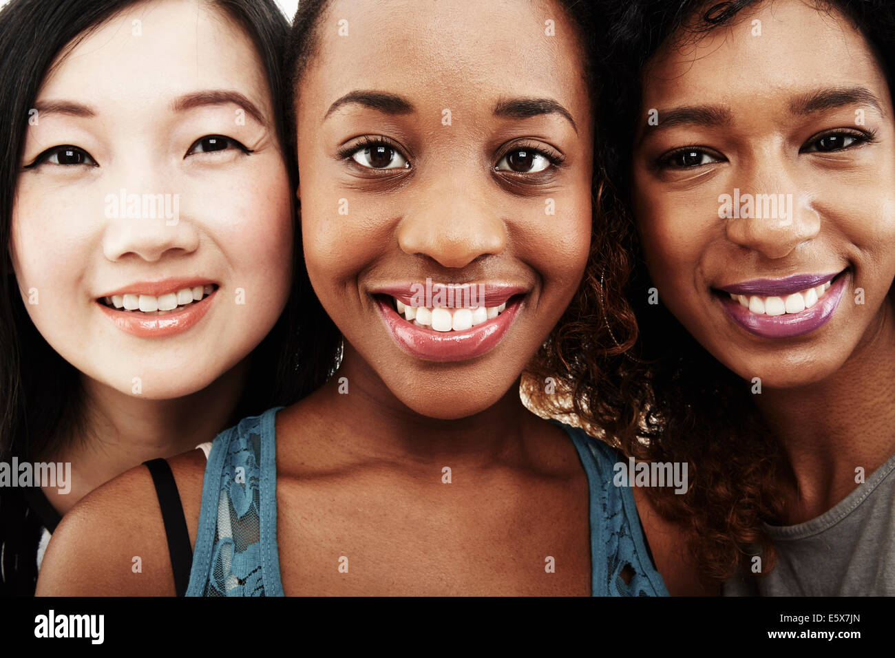 Close up studio portrait of three smiling young women - Stock Image