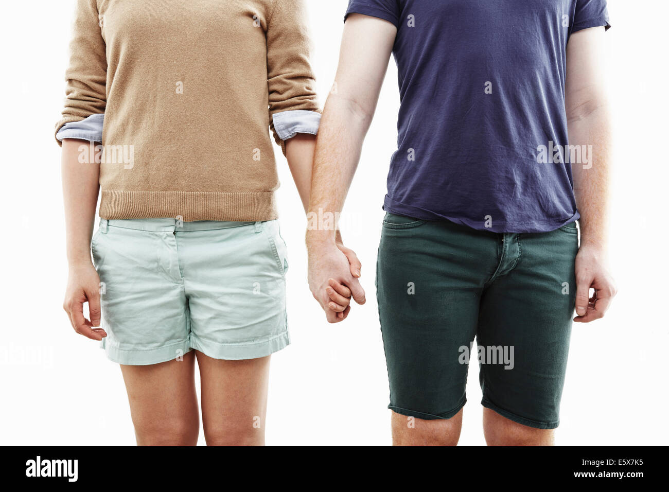 Studio cropped shot of young couple holding hands - Stock Image