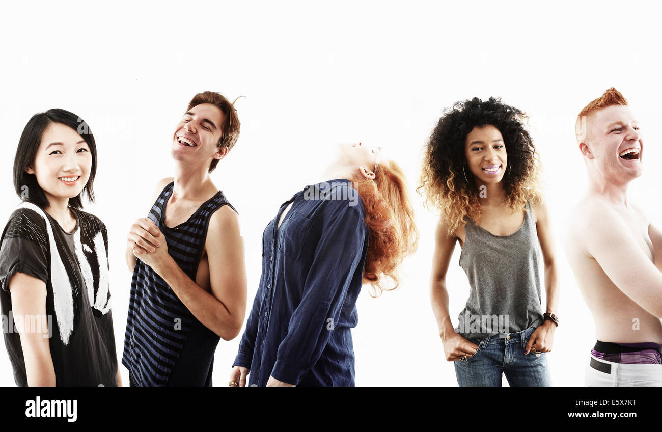 Studio portrait of five smiling young adults in a row - Stock Image