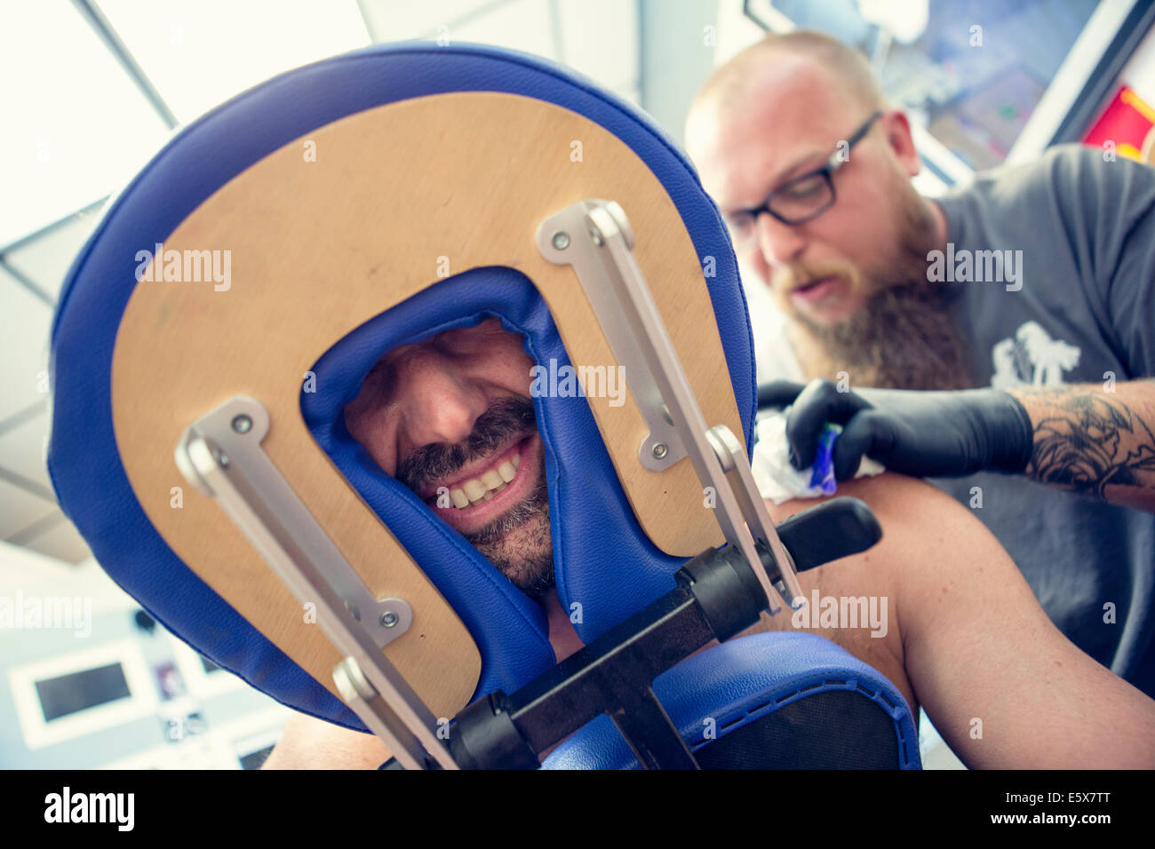 Male customers face between headrest in tattoo parlor - Stock Image