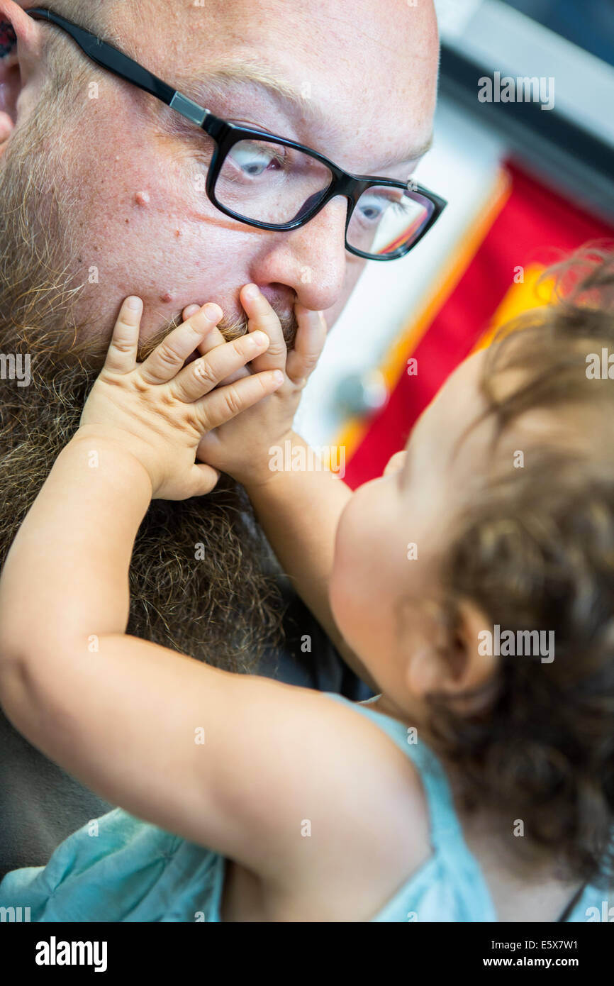 Close up of baby girl with hands over man's mouth - Stock Image