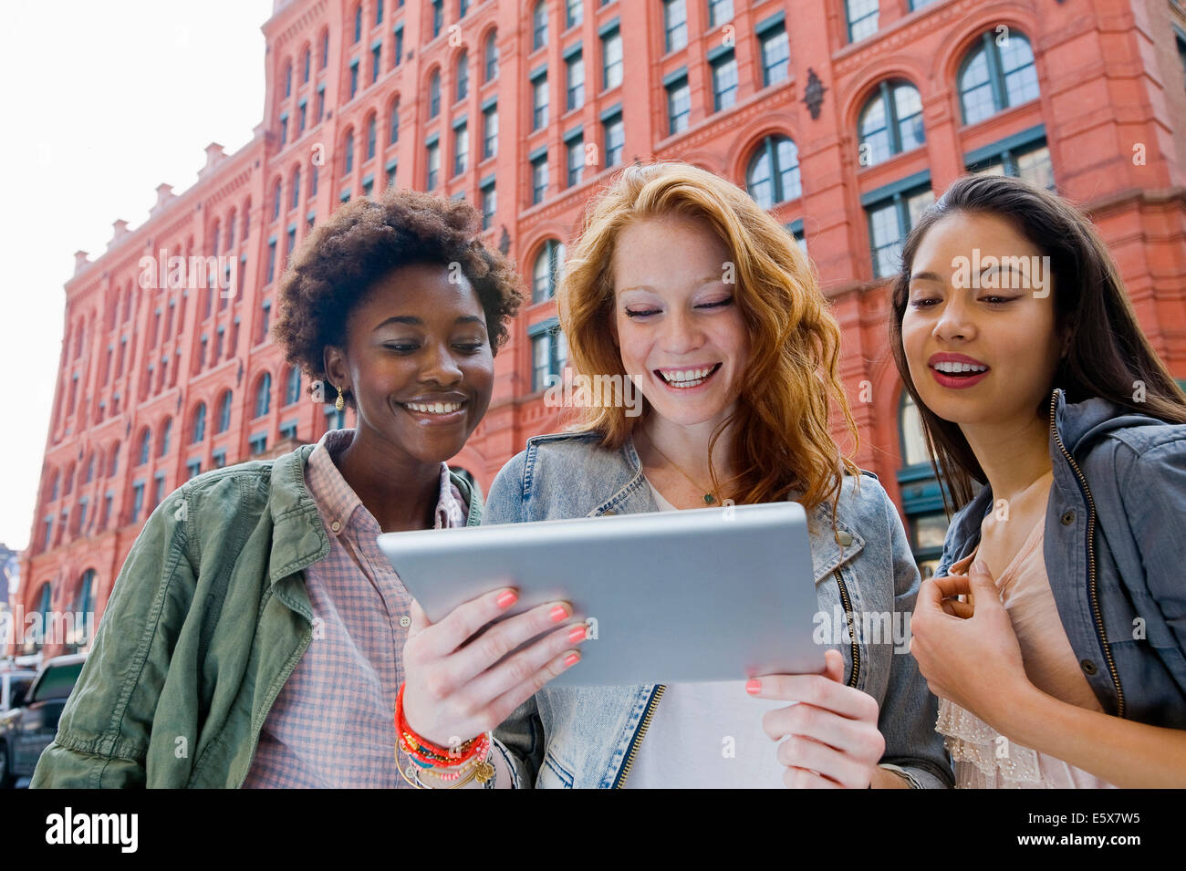 Three young women looking at digital tablet in street - Stock Image