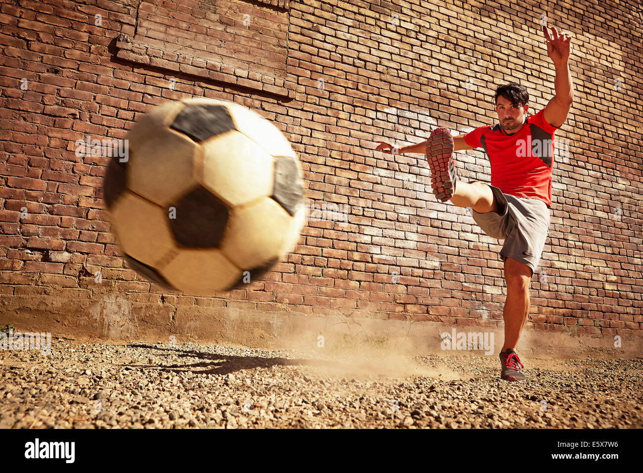 Young man kicking soccer ball on wasteland - Stock Image