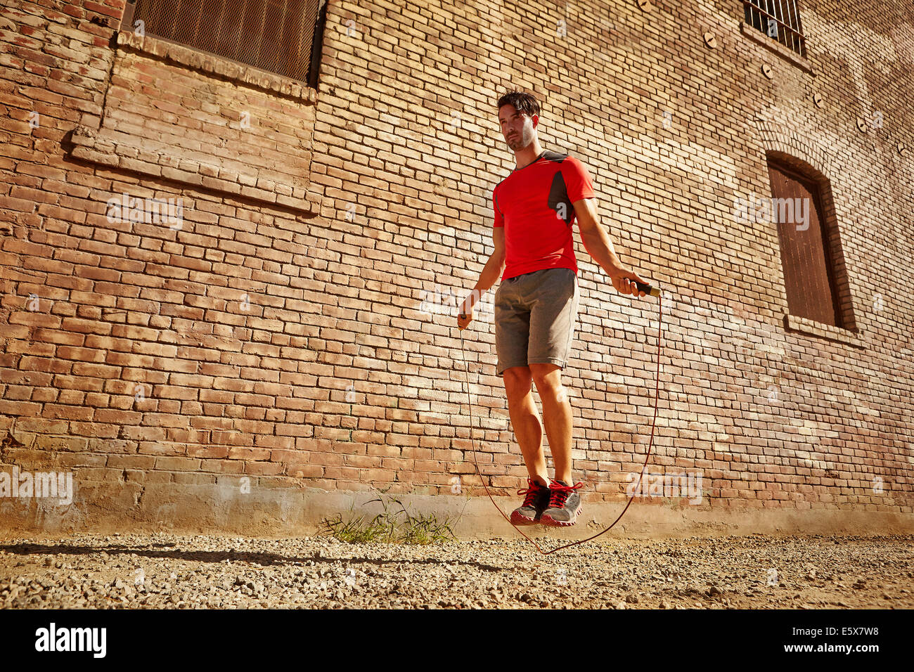 Young man exercising with skipping rope on wasteland - Stock Image