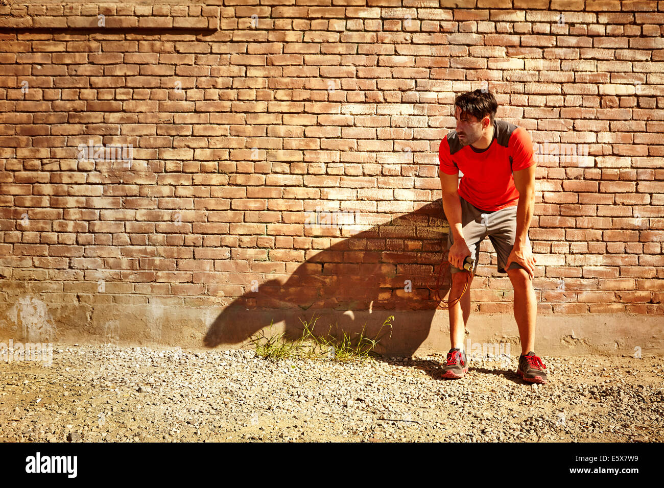 Young male runner taking a break - Stock Image