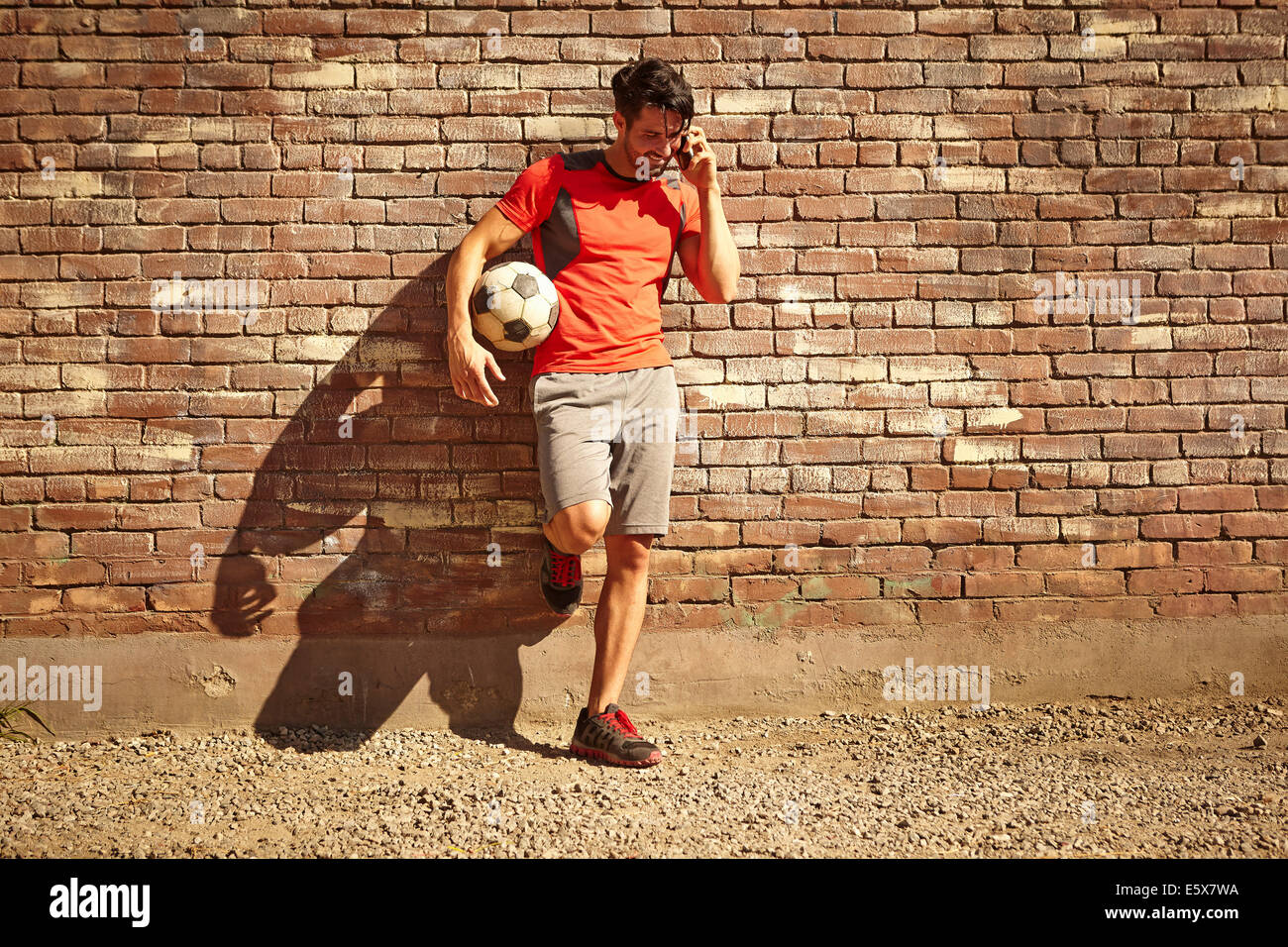 Young male soccer player chatting on smartphone on wasteland - Stock Image