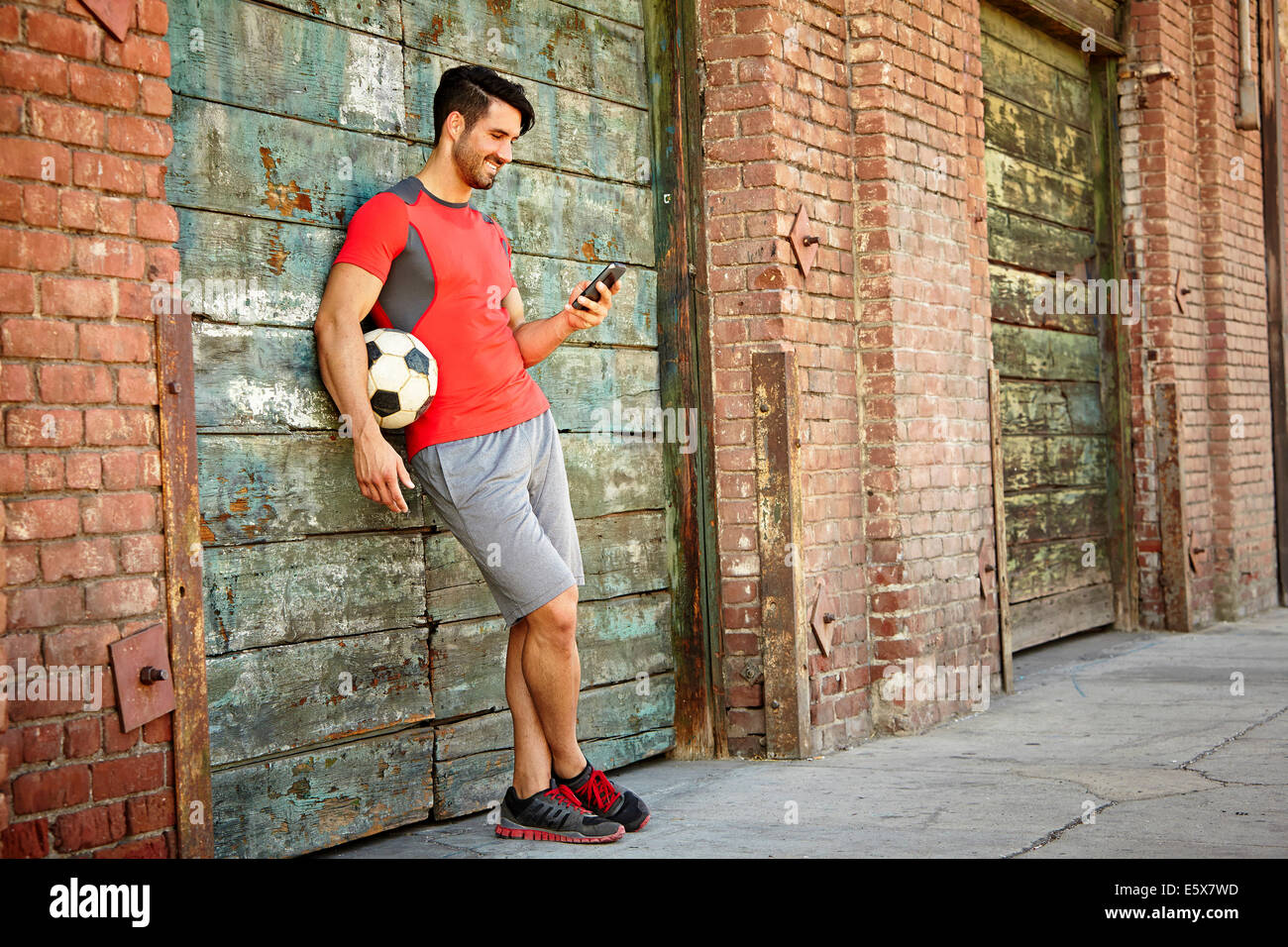 Young male soccer player texting on smartphone - Stock Image