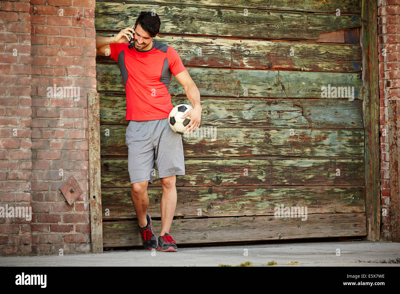 Young male soccer player chatting on smartphone - Stock Image