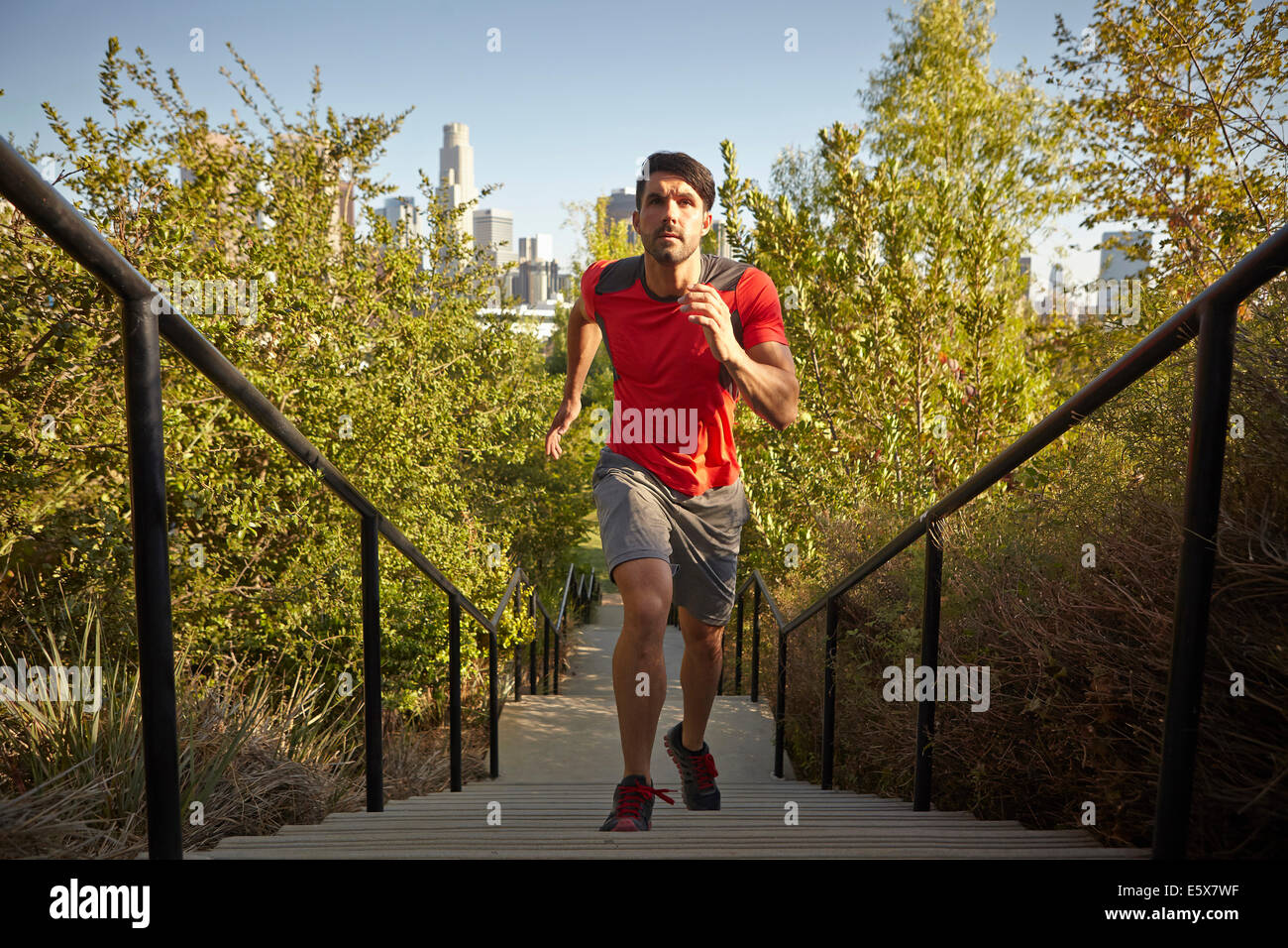 Young male runner running up park steps - Stock Image