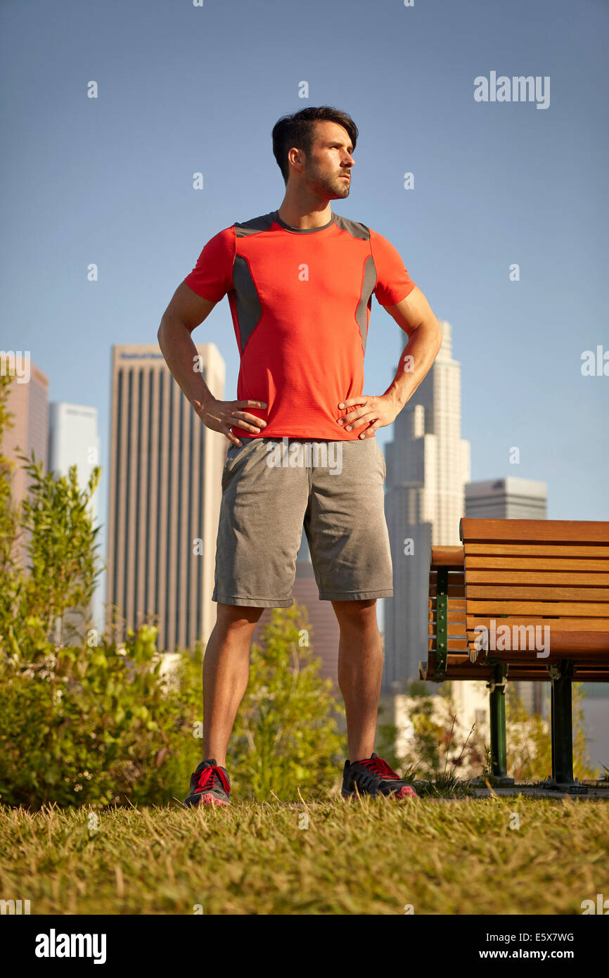 Young male runner taking a break in park - Stock Image