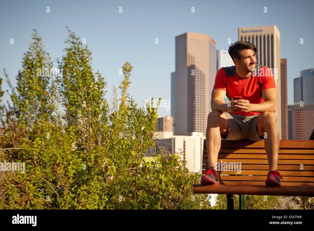 Young male runner taking a break on park bench - Stock Image