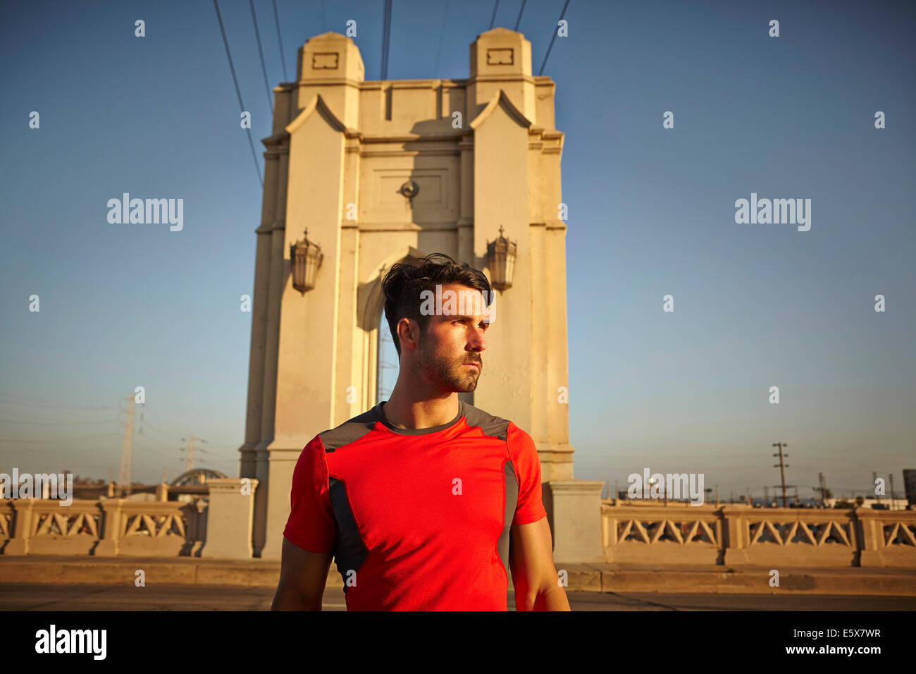 Young male runner taking a break at city bridge - Stock Image