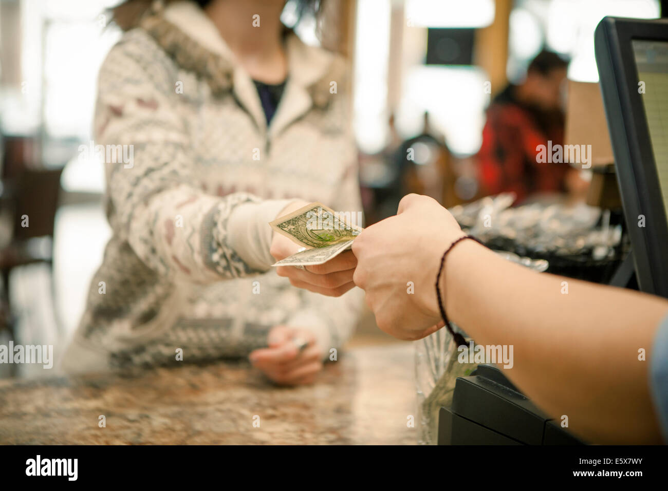 Female customer handing payment to waiter over cafe counter - Stock Image