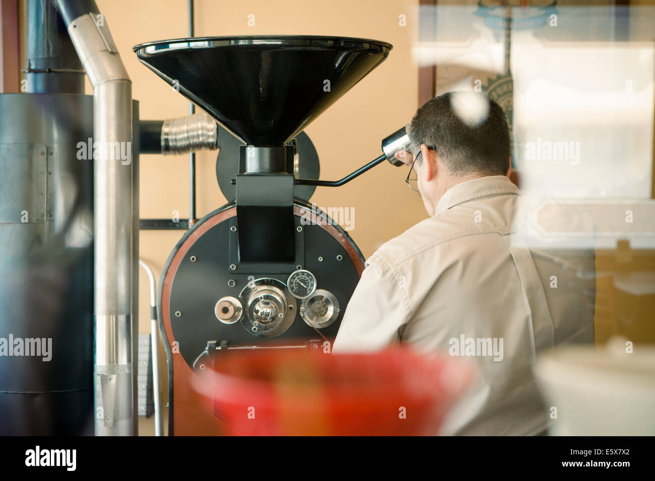Rear view of mature man using coffee roasting machine in cafe - Stock Image