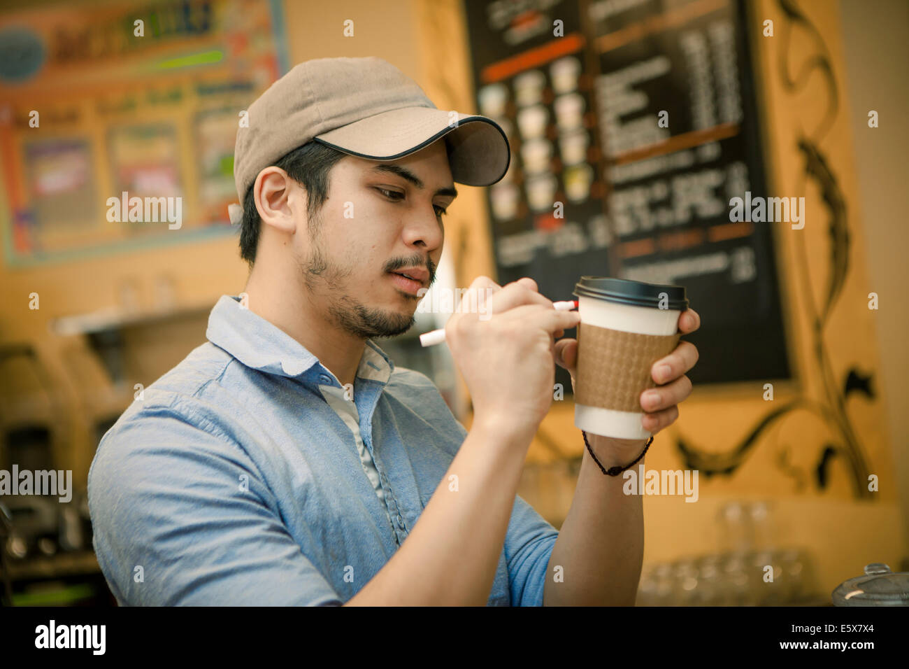 Barista writing on disposable cup in cafe - Stock Image