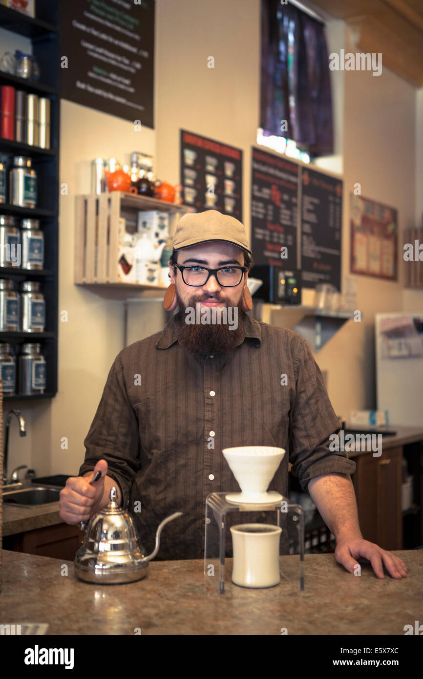 Portrait of barista serving tea on cafe counter - Stock Image