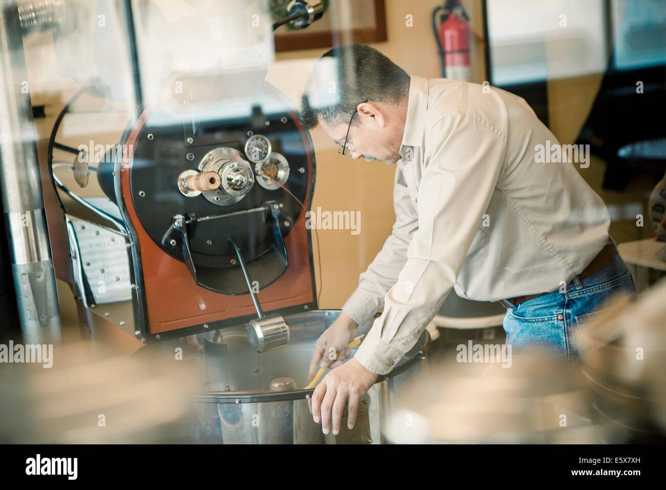Mature man using coffee roasting machine in cafe - Stock Image