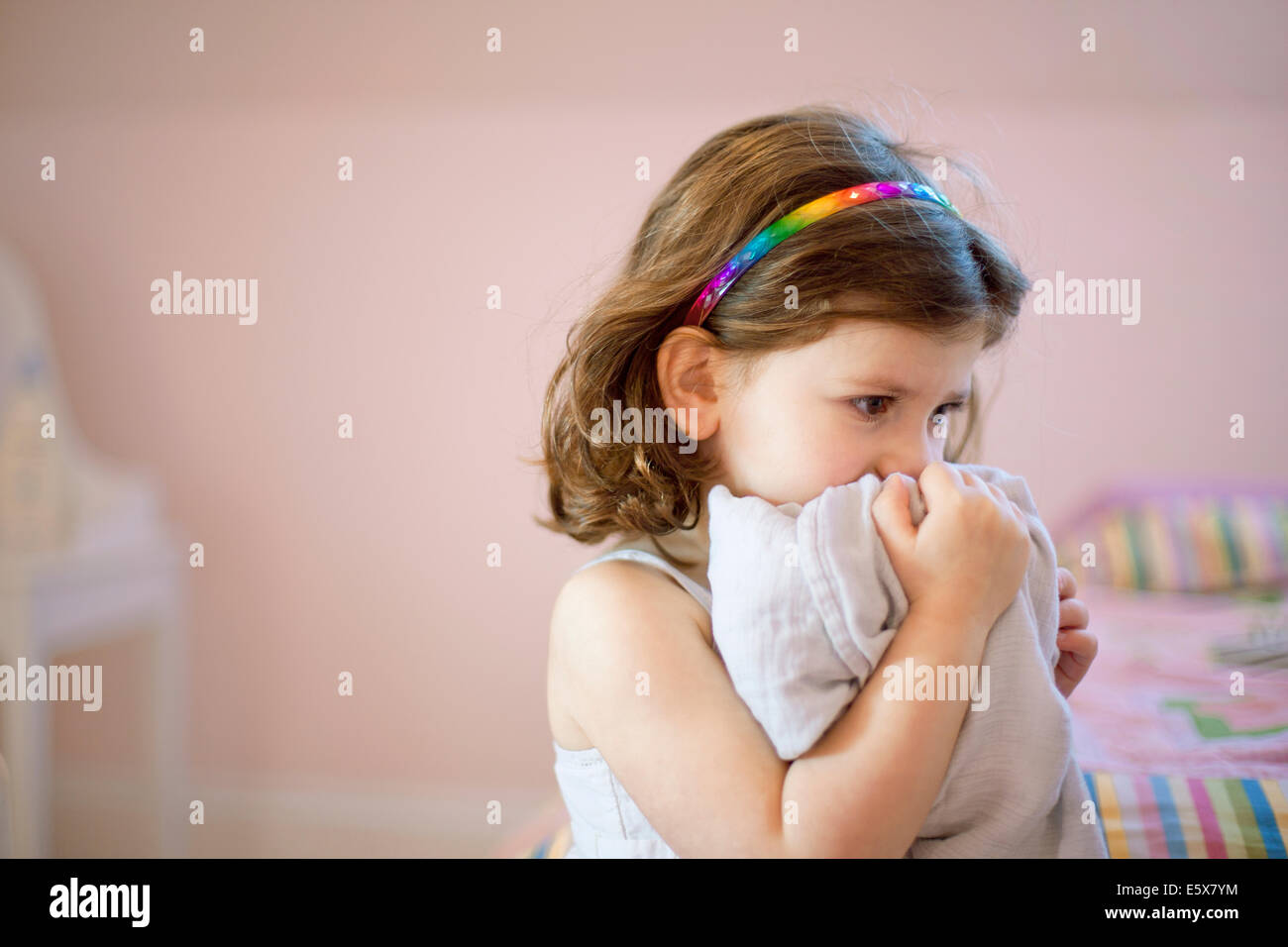 Unhappy three year old girl in bedroom holding comfort blanket to face - Stock Image