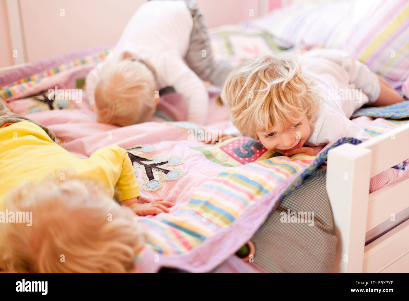 Three young brothers crawling face down on bed - Stock Image