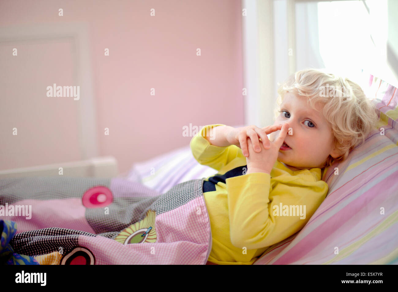 Male toddler lying in bed making secret hand gesture sign - Stock Image