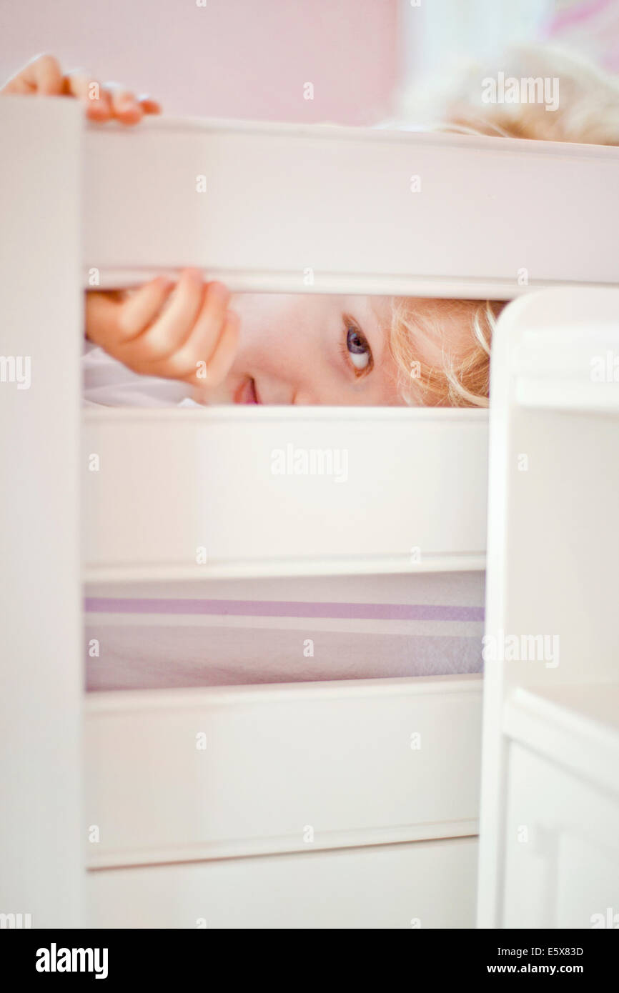 Close up portrait of four year old boy peeking through bed frame - Stock Image