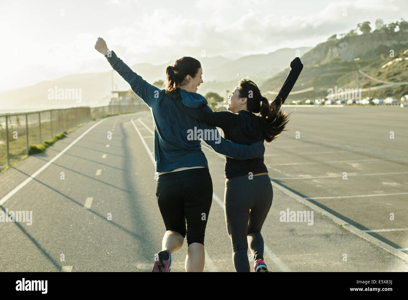 Joggers cheering on road - Stock Image