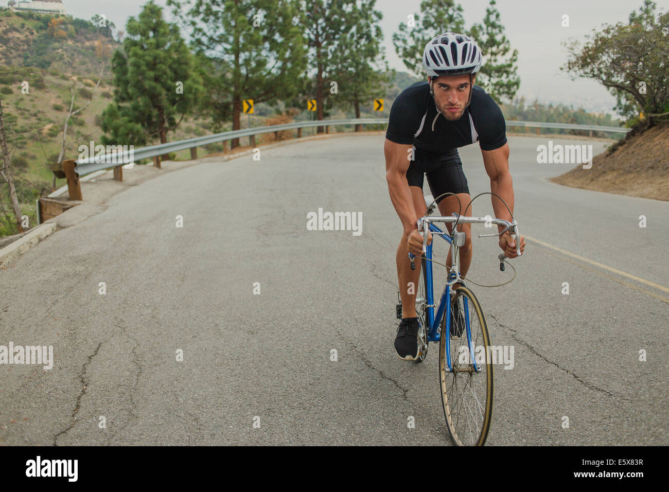 Cyclist on uphill road - Stock Image
