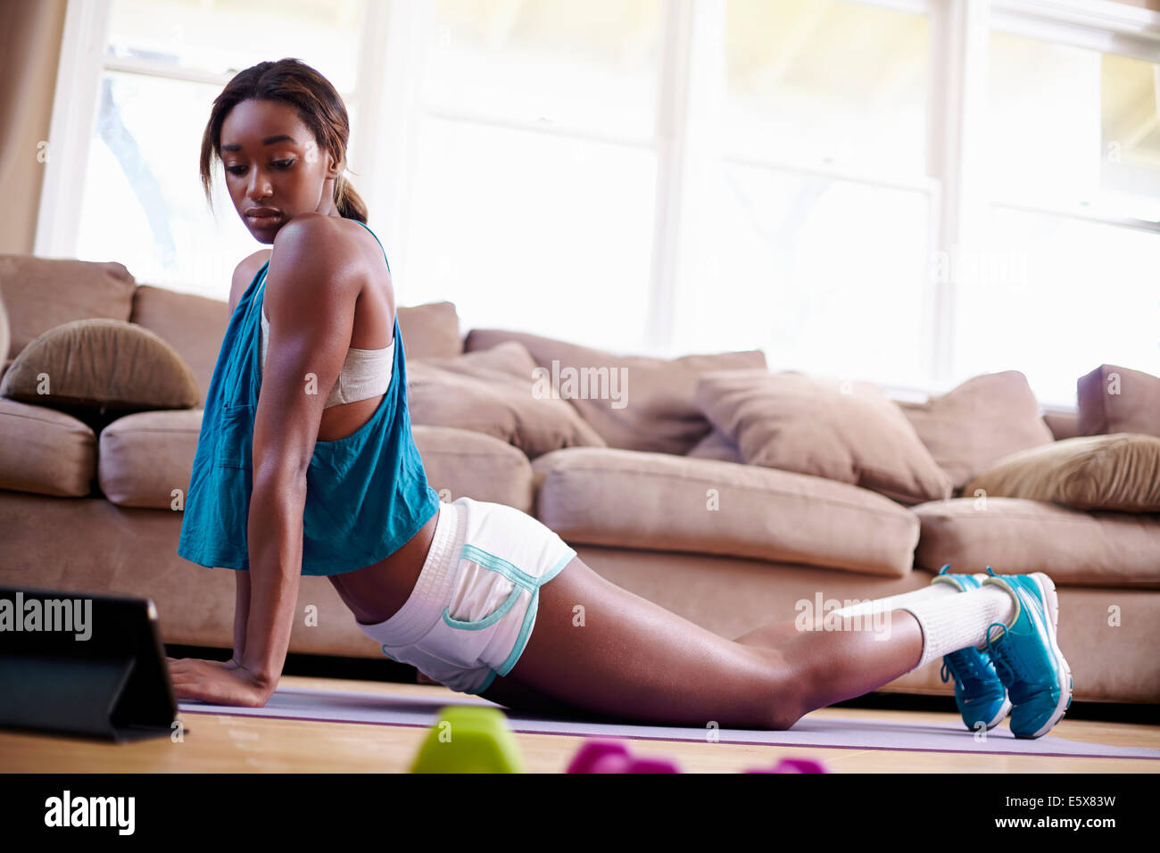 Young woman exercising on sitting room floor whilst looking at instruction on digital tablet - Stock Image