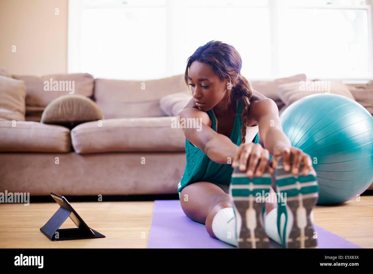 Young woman exercising on sitting room floor whilst looking at digital tablet - Stock Image